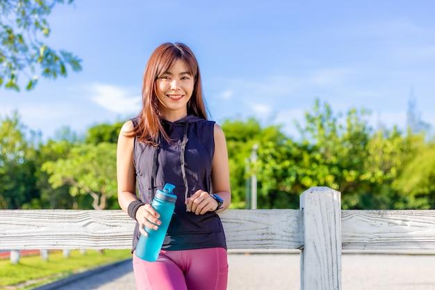 Feliz bella mujer asiática joven apoyándose en la valla de madera blanca y sonriendo a la cámara mientras toma su descanso de agua