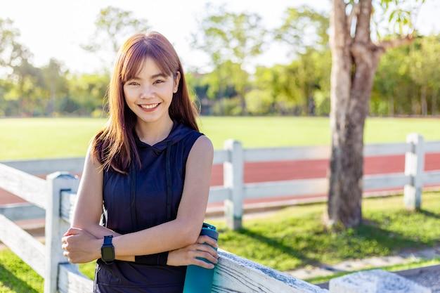 Feliz bella mujer asiática joven sonriendo a la cámara, de pie y sosteniendo su botella de agua