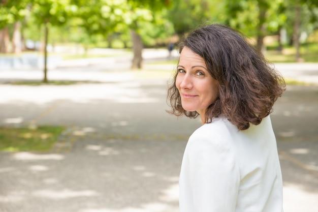 Feliz bella mujer caminando en el parque