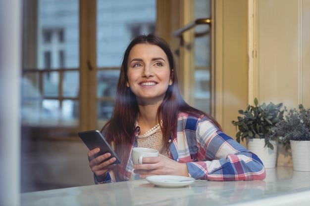 Feliz bella mujer con celular en café