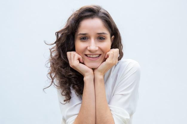 Feliz bella mujer inclinada barbilla y cabeza en las manos