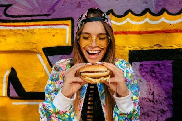 Feliz bella mujer joven, sonriendo ampliamente, tiene sabrosa hamburguesa en dos manos.