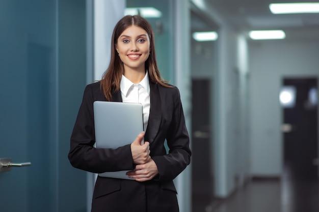 Feliz bella mujer de negocios en el hall de la oficina con un ordenador portátil