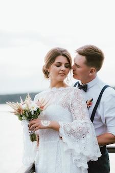 Feliz besando a la pareja de recién casados