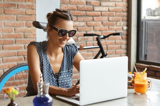 Feliz blogger femenina escribiendo una nueva publicación en su blog, usando una conexión a internet de alta velocidad, sentada a la mesa con aparatos electrónicos, comida y jugo fresco
