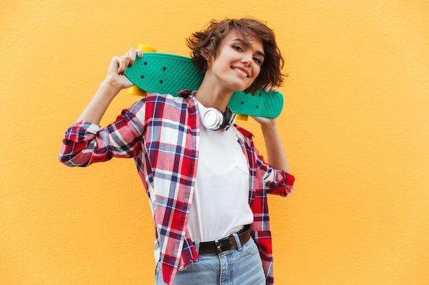 Feliz bonita adolescente sosteniendo patineta sobre sus hombros