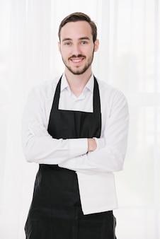 Feliz camarero de pie con las manos cruzadas