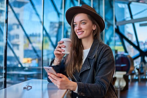 Feliz casual alegre elegante mujer casual con sombrero con teléfono móvil tiene taza de papel durante el consumo de café y relajarse en la cafetería. estilo de vida de la gente moderna