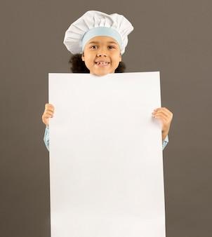 Feliz chef sosteniendo pancarta en blanco