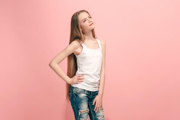 Feliz chica adolescente de pie, sonriendo aislado en estudio rosa de moda.