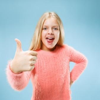 Feliz chica adolescente de pie, sonriendo aislado sobre fondo de estudio azul de moda. hermoso retrato femenino. los jóvenes satisfacen a la chica con el signo ok. las emociones humanas, el concepto de expresión facial. vista frontal.