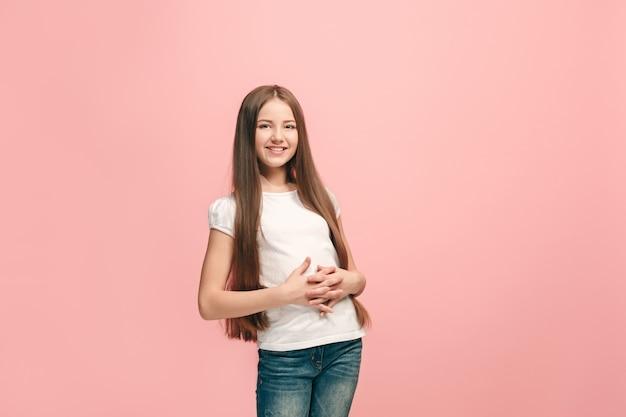 Feliz chica adolescente de pie, sonriendo aislado sobre fondo de estudio rosa de moda.