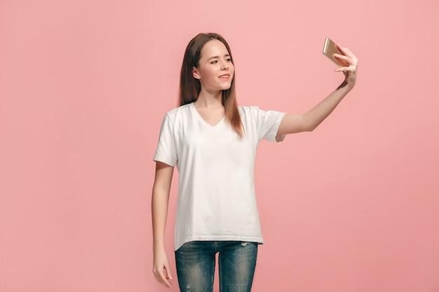 Feliz chica adolescente de pie, sonriendo en estudio rosa, haciendo foto selfie por teléfono móvil.