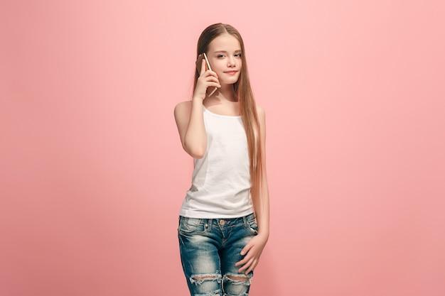 Feliz chica adolescente de pie, sonriendo con teléfono móvil sobre estudio rosa de moda.