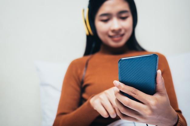 Feliz chica asiática con hehadphones escuchando música.