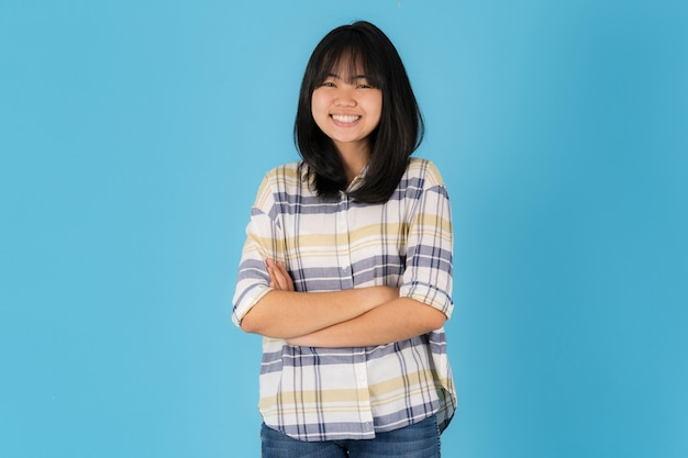 Feliz chica asiática de pie sobre un fondo azul.