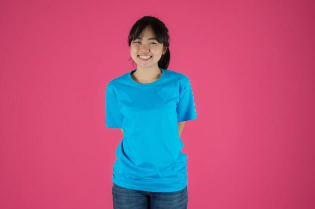 Feliz chica asiática de pie sobre fondo rosa