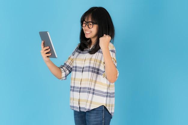 Feliz chica asiática de pie con el uso de tableta sobre un fondo azul.