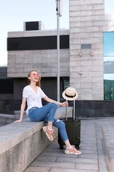 Feliz chica atractiva en vasos con equipaje se encuentra en verano