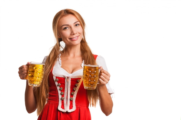 Feliz chica bávara sonriendo a la cámara, sosteniendo jarras de cerveza. atractiva mujer alemana en traje tradicional oktoberfest sirviendo cervezas, espacio de copia