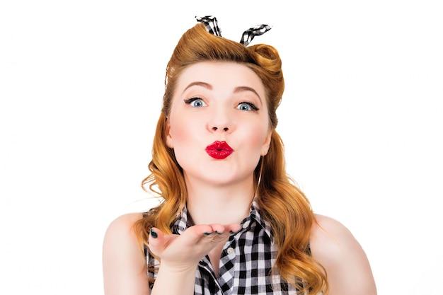 Feliz chica bonita pin up enviando un beso sobre blanco