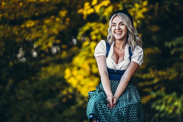 Feliz chica bonita rubia en vestidos típicos, vestido tradicional del festival de la cerveza, sentado al aire libre con coloridos árboles borroneados detrás