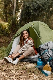 Feliz chica de camping en el bosque atando sus cordones vista larga