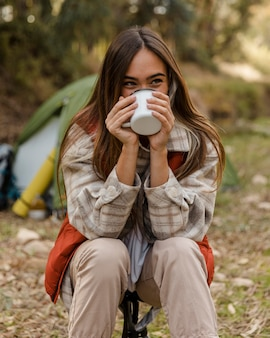 Feliz chica de camping en el bosque bebiendo de una taza