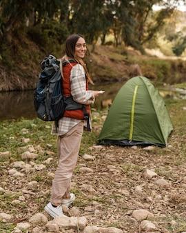 Feliz chica de camping en el bosque y carpa