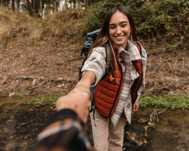 Feliz chica de camping en el bosque cogidos de la mano