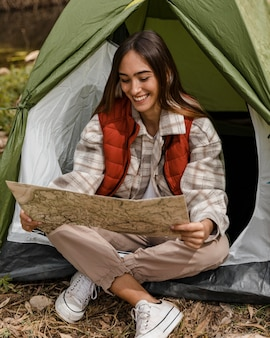 Feliz chica de camping en el bosque comprobando el mapa y sonrisas