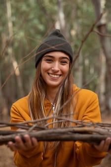 Feliz chica de camping en el bosque con maderas