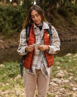 Feliz chica de camping en el bosque mediante teléfono móvil