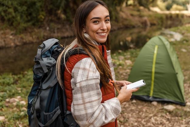 Feliz chica de camping en el bosque y tienda de campaña