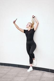 Feliz chica deportiva rubia sonriendo suavemente, tomando selfie y escuchar música. disparar sobre fondo de pared blanca al aire libre. concepto de vida activa y saludable.
