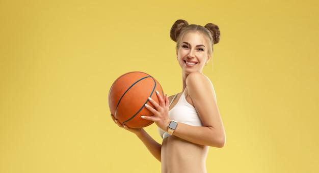 Feliz chica excitada vistiendo pantalones vaqueros sosteniendo una pelota de baloncesto en la pared amarilla