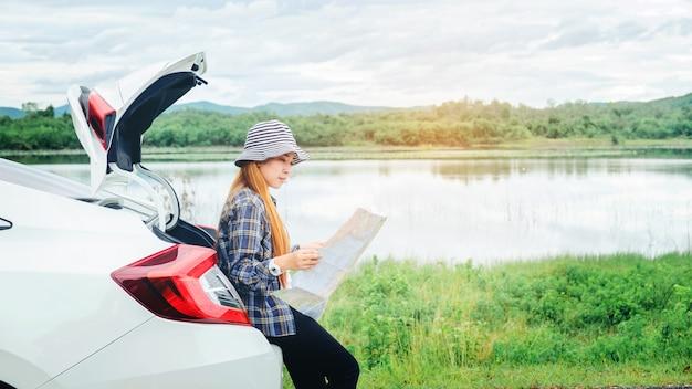 Feliz chica hermosa que viaja en un coche con portón trasero con mapa