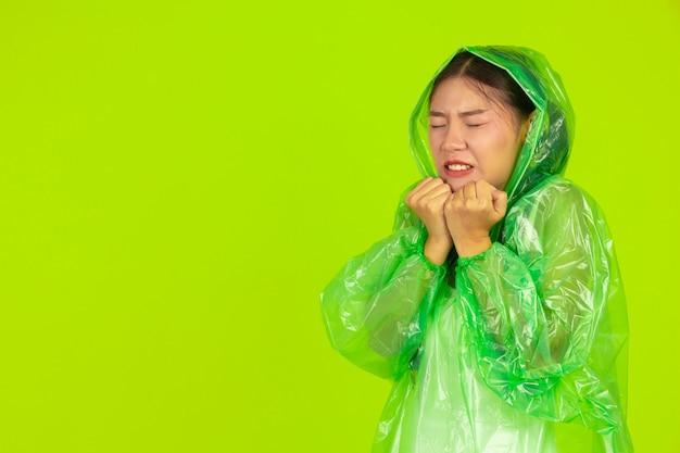 Feliz chica hermosa, vistiendo ropa verde, paraguas y abrigo, día lluvioso.