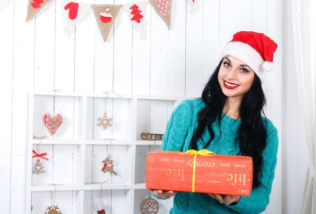 Feliz chica hispana sentada en navidad decorado interior vestida con sombrero de santa claus con una caja de regalo roja.