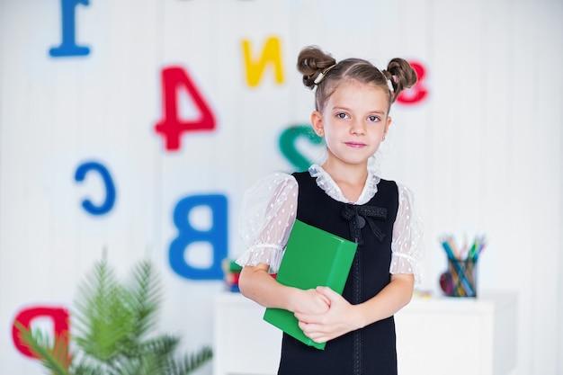 Feliz chica inteligente en uniforme escolar mantenga el libro y mire a la cámara.