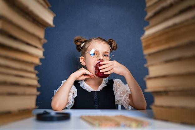 Feliz chica inteligente en vasos redondeados, comiendo una manzana roja mientras está sentada entre dos pilas de libros y mira a la cámara sonriendo.