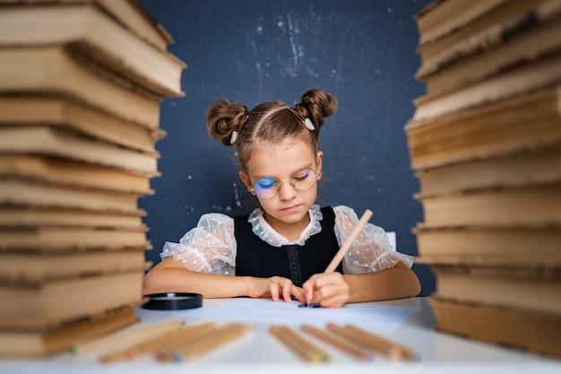 Feliz chica inteligente en vasos redondeados, escribiendo, dibujando mientras está sentado entre dos pilas de libros.