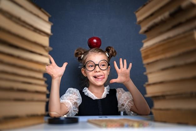Feliz chica inteligente en vasos redondeados con manzana roja en la cabeza sentada entre dos pilas de libros, divertirse y mirar a la cámara sonriendo.