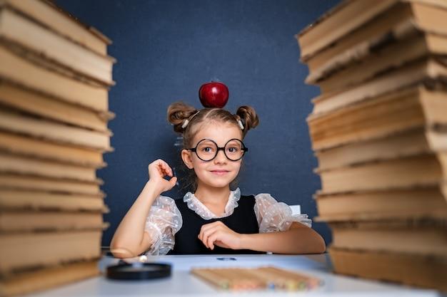 Feliz chica inteligente en vasos redondeados sentado entre dos pilas de libros con manzana roja en la cabeza y mira a la cámara sonriendo.