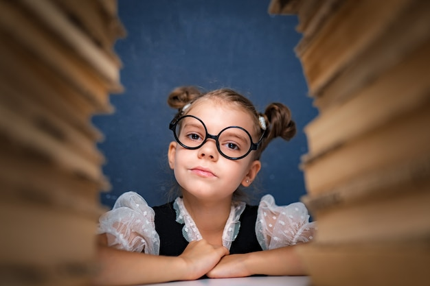 Feliz chica inteligente en vasos redondeados sentado entre dos pilas de libros y mira a la cámara sonriendo.