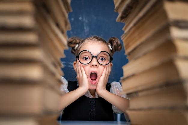 Feliz chica inteligente en vasos redondeados sentado entre dos pilas de libros y mira a la cámara sorprendida.
