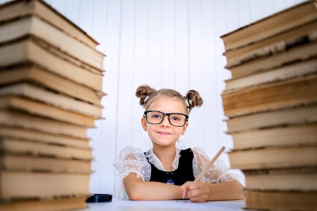 Feliz chica inteligente en vasos redondeados, sosteniendo un lápiz en la mano listo para escribir sentado entre dos pilas de libros y mirar a la cámara sonriendo.