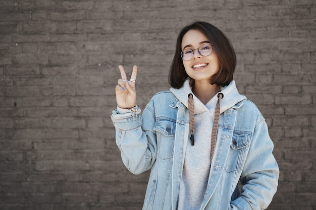 Feliz chica lgbt amigable, mostrando el signo de la paz y sonriendo despreocupada, de pie sobre una pared de ladrillo, inscrita en una universidad increíble, lista para comenzar la vida estudiantil, caminando al aire libre con amigos.