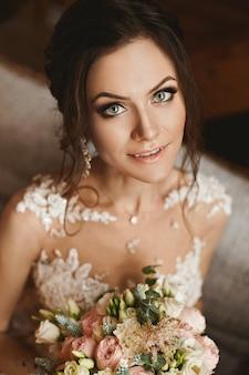Feliz chica modelo morena con peinado de novia y con hermosos ojos en elegante vestido de encaje con un ramo de flores en sus manos posando en el interior