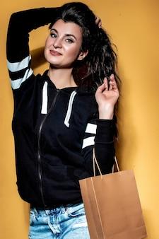 Feliz chica morena tiene una compra en una bolsa de artesanía sobre un fondo naranja.